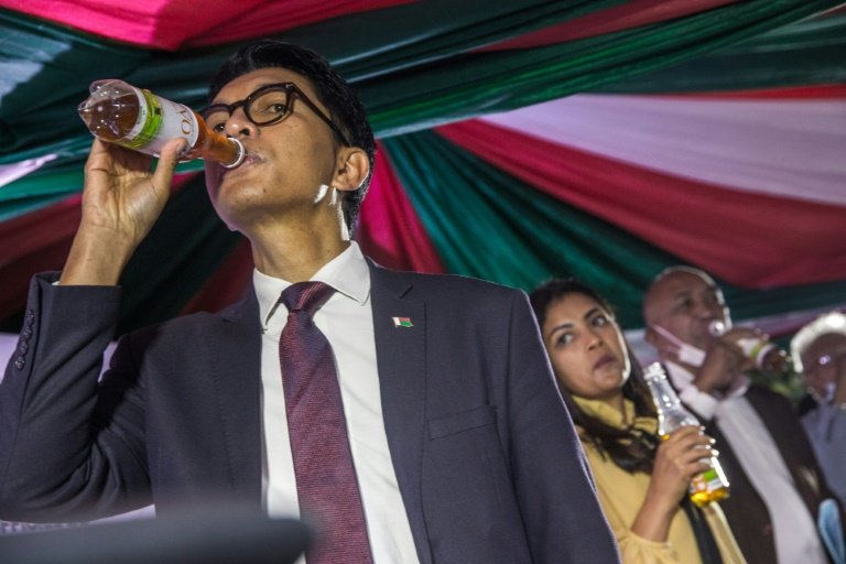 Promoter President Andry Rajoelina drinks from a bottle of Covid Organics at the product's launch on April 22