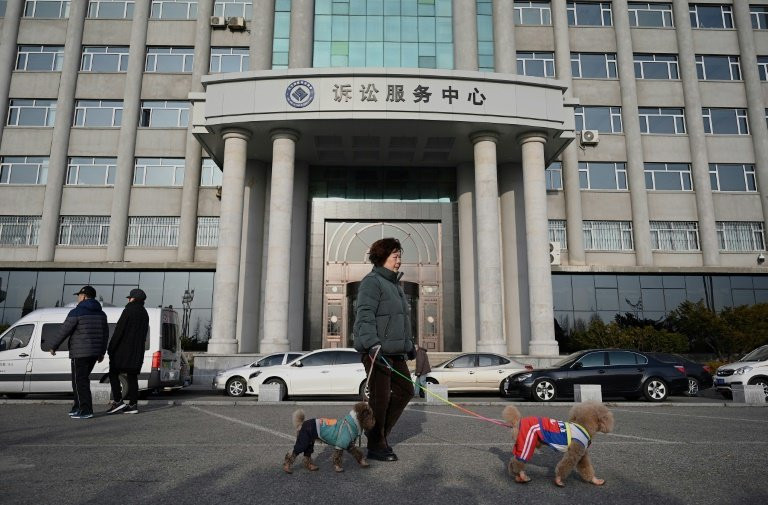 People walk in front of the Dandong Intermediate People's Court where Canadian businessman Michael Spavor willgo on trial     AFP